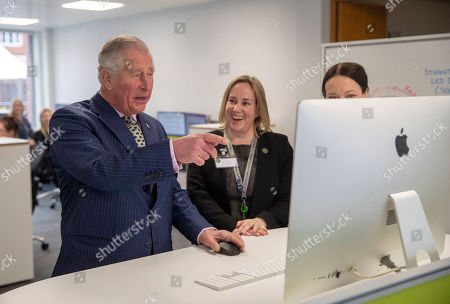 Prince Charles (left) with Lynne Downey (centre) and Kate Lindsey (right), tries out parts of an online course during a visit to the University College of Estate Management's headquarters in Reading, Berkshire, to celebrate of its centenary year