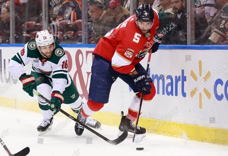 Jason Zucker, Aaron Ekblad. Minnesota Wild left wing Jason Zucker (16) and Florida Panthers defenseman Aaron Ekblad (5) battle for the puck during the first period of an NHL hockey game, in Sunrise, Fla