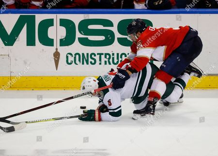 Ryan Donato, Aaron Ekblad. Florida Panthers defenseman Aaron Ekblad, right, and Minnesota Wild center Ryan Donato battle for the puck during the third period of an NHL hockey game, in Sunrise, Fla