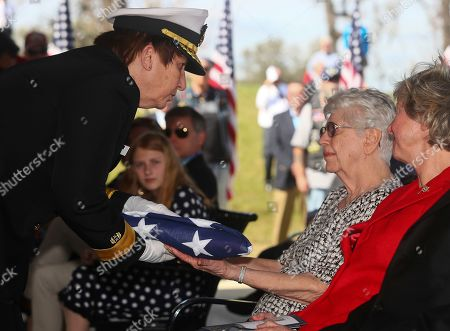 Navy Rear Adm. Carol Lynch presents the flag to Emily Golz at a Service of Honor for her brother Seaman 1st Class Earl Paul Baum, at the Tallahassee National Cemetery, in Tallahassee, Fla. Baum was killed in action on Dec. 7, 1941, when the battleship USS Oklahoma was attacked on the U.S. Navy Base at Pearl Harbor, Oahu, Hawaii. His remains were identified by the Navy last September through DNA samples given by relatives. Baum is the first soldier killed in action to be buried at the cemetery