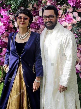 Bollywood actor Aamir Khan and wife Kiran Rao stand for photographs as they arrive for the wedding of Akash Ambani, son of Reliance Industries Chairman Mukesh Ambani, in Mumbai, India