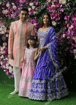 Bollywood actor Abhishek Bachchan, his wife Aishwarya Rai Bachchan and daughter Aradhya stand for photographs as they arrive for the wedding of Akash Ambani, son of Reliance Industries Chairman Mukesh Ambani, in Mumbai, India