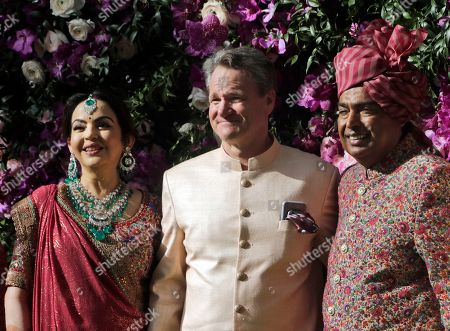 Reliance Industries Chairman Mukesh Ambani, right, and his wife Nita Ambani stand with Brian Moynihan, Chairman and CEO of Bank of America, for a photograph during the wedding of their son Akash Ambani in Mumbai, India