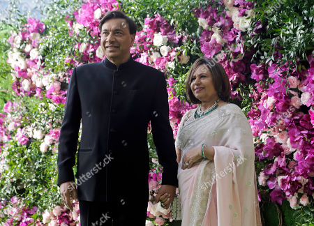 CEO of ArcelorMittal Lakshmi Mittal and his wife Usha Mittal stand for photographs as they arrive for the wedding of Akash Ambani, son of Reliance Industries Chairman Mukesh Ambani, in Mumbai, India