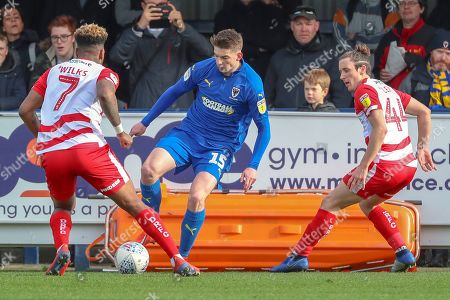 AFC Wimbledon defender Steve Seddon (15) taking on Doncaster Rovers attacker Mallik Wilks (7) and Doncaster Rovers defender Aaron Lewis (44) during the EFL Sky Bet League 1 match between AFC Wimbledon and Doncaster Rovers at the Cherry Red Records Stadium, Kingston