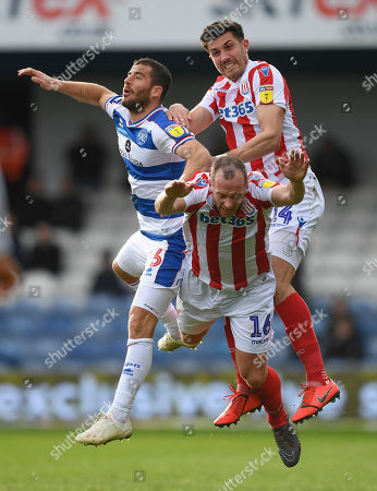 Charlie Adam of Stoke City is pushed by Danny Batth of Stoke City and Tomer Hemed of Queens Park Rangers as they go for the ball