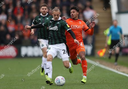Oscar Threlkeld of Plymouth Argyle  holds off   James Justin of Luton Town