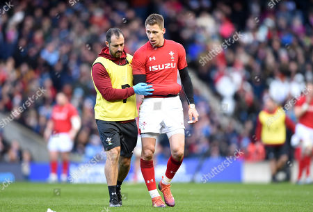 Liam Williams of Wales leaves the field with physio John Miles.
