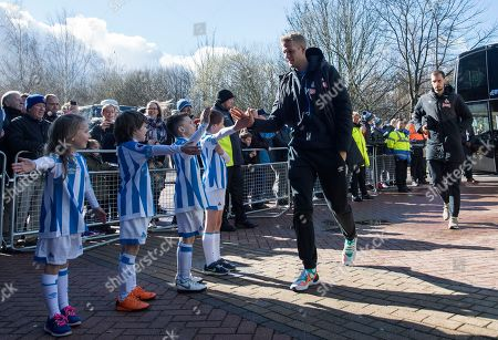 Jonas Lossl goalkeeper of Huddersfield Town meets children as he arrives for the game