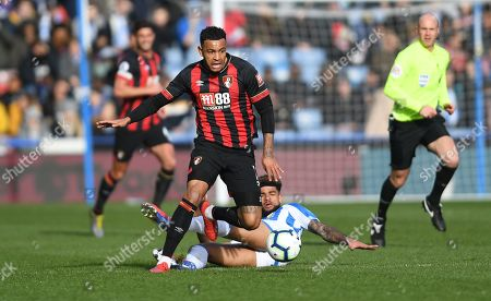 Joshua King of Bournemouth evades the tackle of  Philip Billing of Huddersfield Town