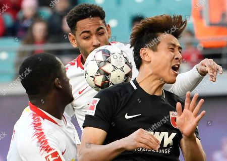Augsburg's Ja-Cheol Koo, right, challenges for the ball against Leipzig's Cunha Matheus, center, during the German first division Bundesliga soccer match between RB Leipzig and FC Augsburg in Leipzig, Germany