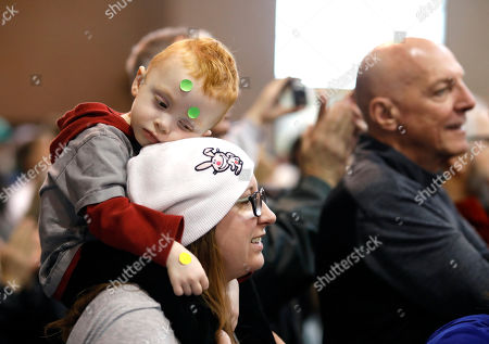 Jude Styron, 3, rests his head his mother Jessica as she listens to 2020 Democratic presidential candidate Sen. Bernie Sanders speaks during a rally, at the Iowa state fairgrounds in Des Moines, Iowa
