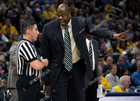 Georgetown head coach Patrick Ewing, right, argues with a referee after a foul against Marquette during the first half of an NCAA college basketball game, in Milwaukee