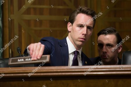 Sen. Josh Hawley, R-Mo., places his nameplate as he listens to an aide during a hearing of the Senate Judiciary Committee on oversight of Customs and Border Protection's response to the smuggling of persons at the southern border, in Washington