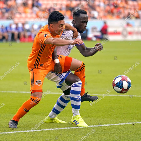 Houston Dynamo's Memo Rodriguez, left, battles Montreal Impact's Bacary Sagna for the ball during the first half of an MLS soccer match, in Houston