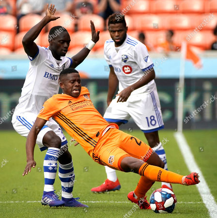 Houston Dynamo's Oscar Garcia, center, tries to keep the ball from Montreal Impact's Michael Azira, left, during the first half of an MLS soccer match, in Houston