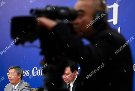 Stock Image of Yi Gang (L), Governor of the People's Bank of China (PBOC) and Chen Yulu (C, back), Deputy governor of PBOC, listens to a reporter's question during a press conference on the sideline of the second session of the 13th National People's Congress (NPC) in Beijing, China, 10 March 2019.