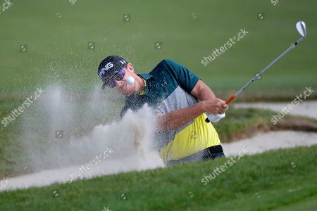 Hunter Mahan hits out of a bunker onto the ninth green during the final round of the Arnold Palmer Invitational golf tournament, in Orlando, Fla