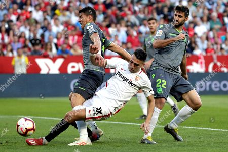 Sevilla's Munir El Haddadi (C) vies for the ball against Real Sociedad's Raul Navas (R) and Hector Moreno (L) during the Spanish LaLiga soccer match between Sevilla and Real Sociedad at Ramon Sanchez Pizjuan stadium in Seville, Andalusia, Spain, 10 March 2019.