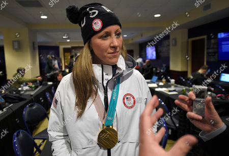 Meghan Duggan, of the gold medal winning U.S. women's Olympic hockey team, listens to a question from the media before an outdoor NHL hockey game between the Washington Capitals and the Toronto Maple Leafs, in Annapolis, Md