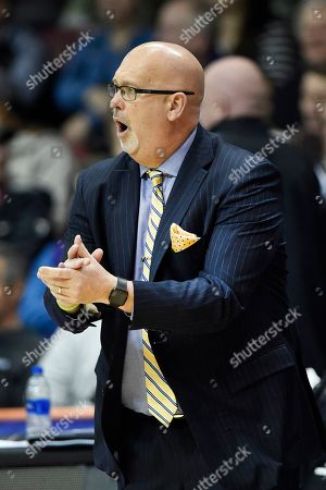 East Tennessee State head coach Steve Forbes cheers on his team in the first half of a semifinal NCAA college basketball game for the Southern Conference tournament championship, in Asheville, N.C