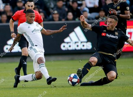 Portland Timbers forward Andy Polo, left, of Peru, and Los Angeles FC forward Christian Ramirez, vie for the ball in the first half of an MLS soccer match in Los Angeles