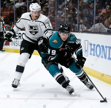 Anaheim Ducks left wing Max Jones, right, controls the puck with Los Angeles Kings defenseman Dion Phaneuf, left, defending during the second period of an NHL hockey game in Anaheim, Calif