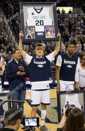Nevada's David Cunningham (20) holds up his framed jersey during senior night before an NCAA college basketball game against San Diego State in Reno, Nev