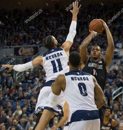Cody Martin, Matt Mitchell. San Diego State forward Matt Mitchell (11) shoots over the out stretched arm of Nevada forward Cody Martin (11) in the first half of an NCAA college basketball game in Reno, Nev