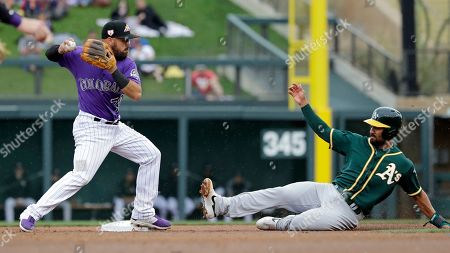 Peter Mooney, Marcus Semien. Colorado Rockies second baseman Peter Mooney, left, throws to first base after forcing out Oakland Athletics' Marcus Semien at second in the second inning of a spring training baseball game, in Scottsdale, Ariz. Athletics' Mark Canha was safe at first on the fielder's choice