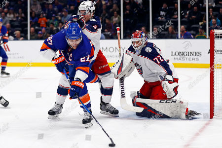 Stock Photo of New York Islanders left wing Anders Lee (27) reaches for the puck as he is shoved by Columbus Blue Jackets defenseman Scott Harrington (4) in front of Rangers goaltender Sergei Bobrovsky during the second period of an NHL hockey game, in Uniondale, N.Y
