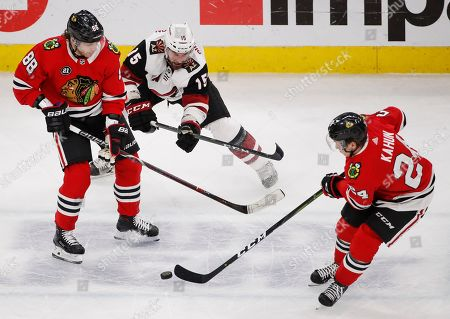 Chicago Blackhawks center Dominik Kahun (24) and right wing Patrick Kane (88) keep the puck away from Arizona Coyotes center Brad Richardson (15) during the first period of an NHL hockey game, in Chicago