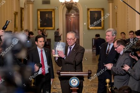 Chuck Schumer, Brian Schatz, Sheldon Whitehouse. Senate Minority Leader Sen. Chuck Schumer of N.Y., center, accompanied by, Sen. Brian Schatz, D-Hawaii, left, and Sen. Sheldon Whitehouse, D-R.I., right, holds up President Donald Trump's 2020 budget as he speaks following a Senate policy luncheon on Capitol Hill in Washington