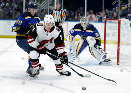 Arizona Coyotes' Nick Cousins controls the puck as St. Louis Blues' Vince Dunn (29) and goaltender Jordan Binnington (50) defend during the first period of an NHL hockey game, in St. Louis