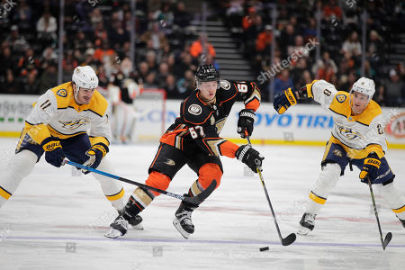 Rickard Rakell, Brian Boyle, Kyle Turris. Anaheim Ducks' Rickard Rakell, center, of Sweden, moves the puck past Nashville Predators' Brian Boyle, left, and Kyle Turris during the second period of an NHL hockey game, in Anaheim, Calif