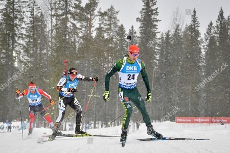 Stock Photo of Arnd Peiffer (R) of Germany followed by Florent Claude (21) of Belgium and Simon Eder of Austria compete during the men's 20km individual competition at the IBU World Biathlon Championships in Oestersund, Sweden, on March 13, 2019.