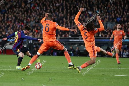 Lionel Messi of Barcelona sends Marcelo of Olympique Lyonnais and Jason Denayer the wrong way on the way to scoring the 3rd goal