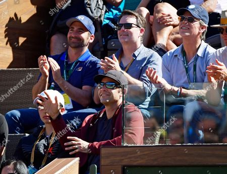 Tennis great Pete Sampras, bottom, waves as the crowd cheers during the Roger Federer-Kyle Edmund match at the BNP Paribas Open tennis tournament, in Indian Wells, Calif. Former NASCAR driver Jeff Gordon is behind him, center, hatless in dark glasses