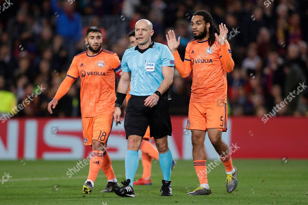 Lyon defender Jason Denayer, right, and Lyon forward Nabil Fekir, left, react to a decision of Polish referee Szymon Marciniak during the Champions League round of 16, 2nd leg, soccer match between FC Barcelona and Olympique Lyon at the Camp Nou stadium in Barcelona, Spain