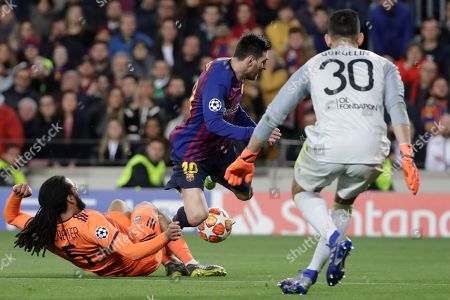 Barcelona's Lionel Messi, centre, is tackled by Lyon's Jason Denayer during the Champions League round of 16, 2nd leg, soccer match between FC Barcelona and Olympique Lyon at the Camp Nou stadium in Barcelona, Spain
