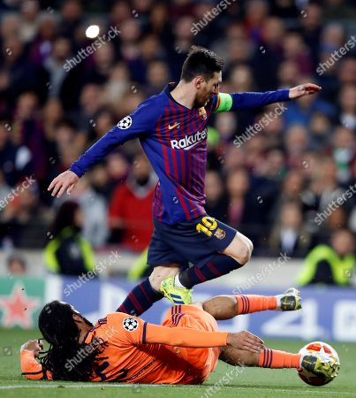 FC Barcelona's forward Leo Messi (top) in action against Jason Denayer (bottom) of Olympique Lyon during the UEFA Champions League round of 16 second leg soccer match between FC Barcelona and Olympique Lyon at Camp Nou in Barcelona, Catalonia, north eastern Spain, 13 March 2019.