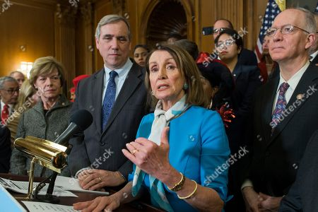 Stock Image of US Speaker of the House Democrat Nancy Pelosi (C) speaks beside Democratic Senator from Wisconsin Tammy Baldwin (L), Democratic Senator from Oregon Jeff Merkley (2-L) and Democratic Representative from Illinois Bill Foster (R); during at an event held to introduce the Equality Act on Capitol Hill in Washington, DC, USA, 13 March 2019. The Equality Act, which has been applauded by members of the LGBTQ community, is legislation that would amend the Civil Rights Act of 1964 to prohibit discrimination on the basis of sexual orientation and gender identity 'in education, employment, housing, credit, federal jury service, public accommodations, and the use of federal funds'.