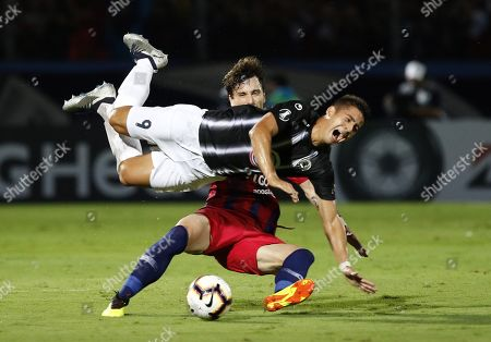 Stock Picture of Cerro's Fernando Amorebieta (down) vies for the ball with Zamora's Guillermo Paiva (top) during their Copa Libertadoers group E soccer match between Club Cerro Porteno of Paraguay and Zamora of Venezuela, at General Pablo Rojas stadium in Asuncion, Paraguay, 13 March 2019.