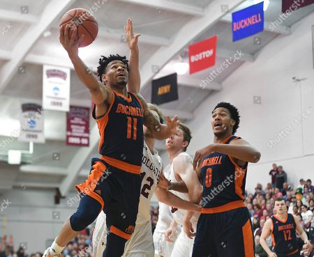 Bucknell guard Avi Toomer, left, drives for a layup past Colgate center Dana Batt as Bucknell center Paul Newman (0) watches during the first half of an NCAA college basketball game for the championship of the Patriot League men's tournament in Hamilton, N.Y
