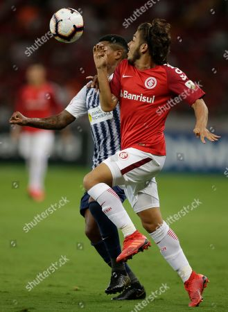 Nonato of Brazil's Internacional, left, fights for the ball with Wilder Cartagena of Peru's Alianza Lima during a Copa Libertadores soccer match at the Beira-Rio stadium in Porto Alegre, Brazil
