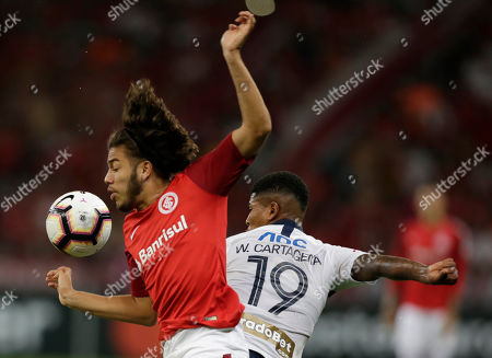 Stock Photo of Nonato of Brazil's Internacional, left, fights for the ball with Wilder Cartagena of Peru's Alianza Lima during a Copa Libertadores soccer match at the Beira-Rio stadium in Porto Alegre, Brazil