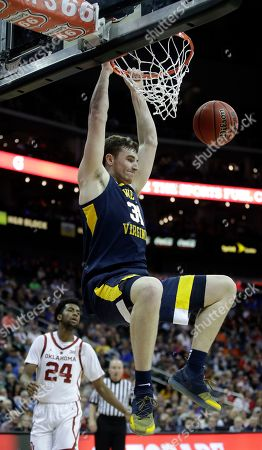 West Virginia's Logan Routt dunks during the first half of an NCAA college basketball game against Oklahoma in the Big 12 men's tournament, in Kansas City, Mo