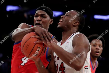 St. John's guard Mustapha Heron (14) tries for a shot against DePaul forward Paul Reed (4) during the first half of an NCAA college basketball game in the Big East men's tournament, in New York