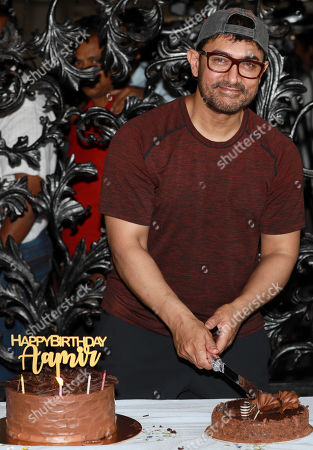 Stock Photo of Bollywood actor Aamir Khan cuts his birthday cake as he celebrates his birthday at his residence at Bandra in Mumbai, India, 14 March 2019. Aamir turned 54.