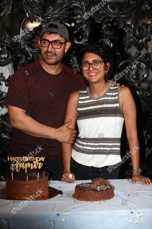 Bollywood actor Aamir Khan (L) and his wife Kiran Rao (R) pose with a birthday cake as he celebrates his birthday at his residence at Bandra in Mumbai, India, 14 March 2019. Aamir turned 54.